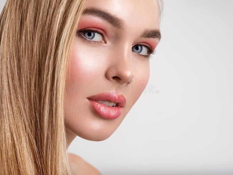 Portrait of a beautiful woman with a coral color makeup. Attractive blond  girl with  bright fashion make-up, posing at studio. stock photos