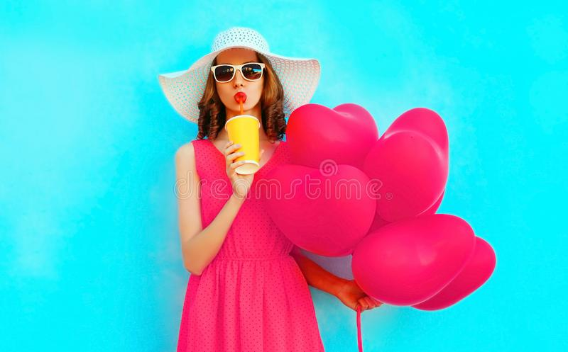 Portrait beautiful woman drinking fruit juice with pink heart shaped balloons on colorful blue background. Wearing summer straw hat royalty free stock images