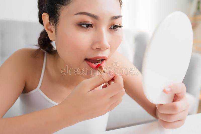 Portrait of a beautiful woman, dyes her lips lipstick pink, looking in the mirror stock photo
