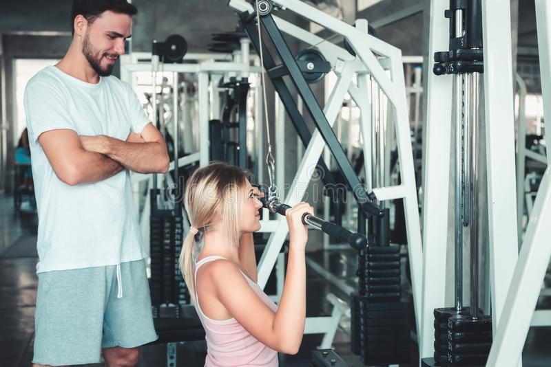 Portrait of Beautiful Woman is Exercised Training With Bodybuilder Machine in Fitness Club., Attractive of Sporty Girl Doing royalty free stock images