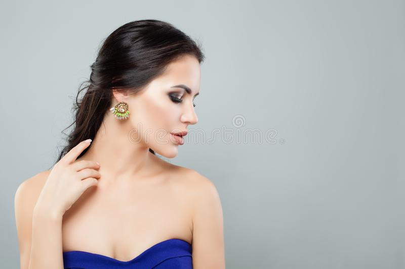 Portrait of beautiful woman in fashion jewelry earrings with green gem and diamond. Female profile.  royalty free stock photo