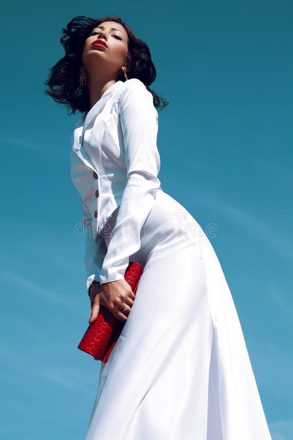 Portrait of a beautiful woman fashion model posing in elegant white atlas cocktail dress with red leather clutch in her hands stock photos