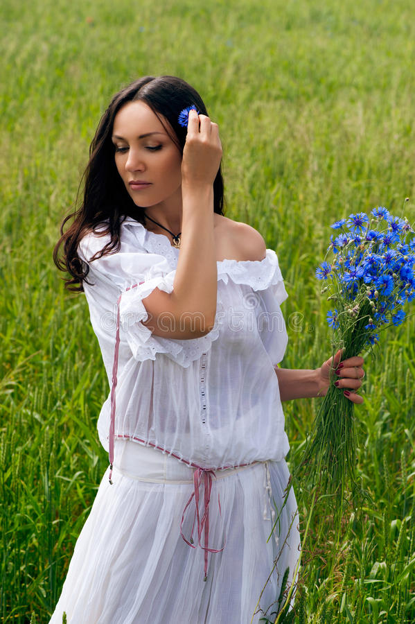 Portrait of beautiful woman with flowers in the field royalty free stock images