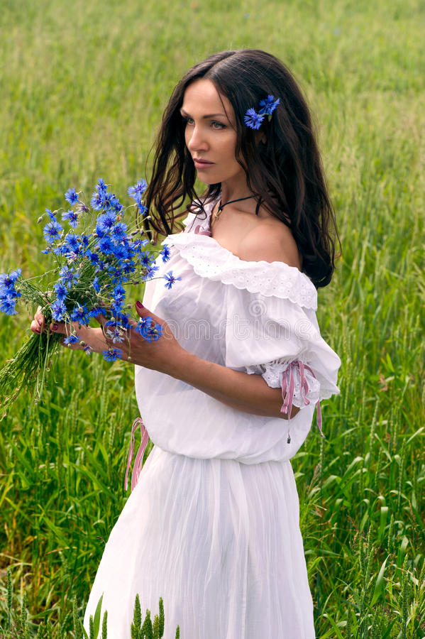 Portrait of beautiful woman with flowers in the field stock images