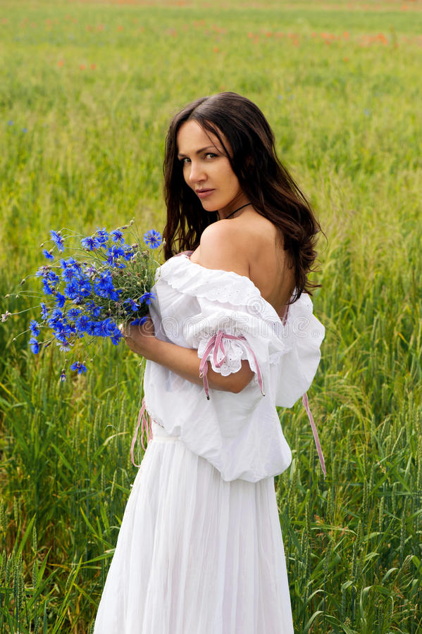 Portrait of beautiful woman with flowers in the field royalty free stock photography