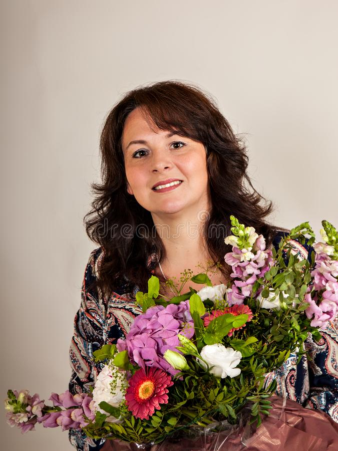 Portrait of beautiful woman with flowers on isolated gray background royalty free stock photo