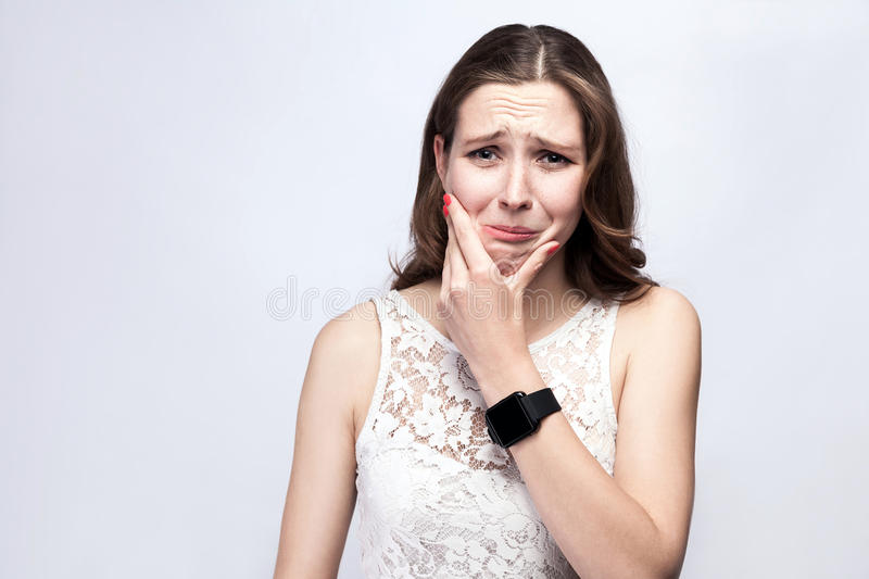 Portrait of beautiful woman with freckles and white dress and smart watch with tooth pain on silver gray background. royalty free stock images
