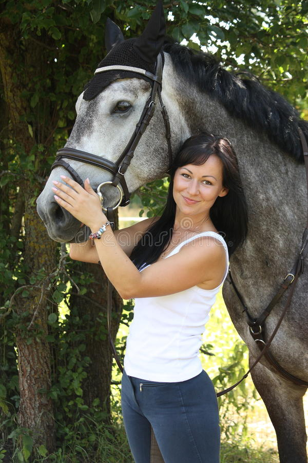 Portrait of beautiful woman and gray horse in garden. Portrait of beautiful young woman and gray horse in garden stock photos