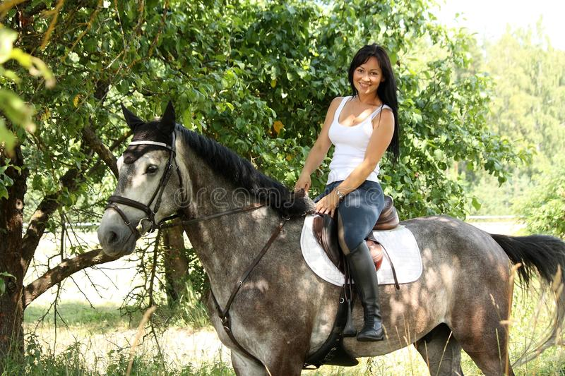 Portrait of beautiful woman and gray horse in garden royalty free stock photo