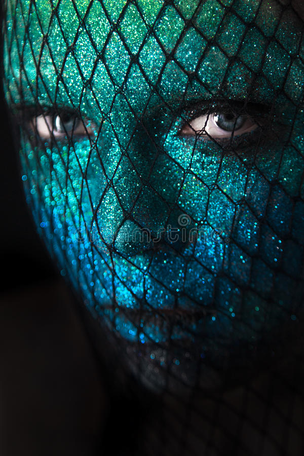 Portrait of beautiful woman with green and blue sparkles on her royalty free stock photo