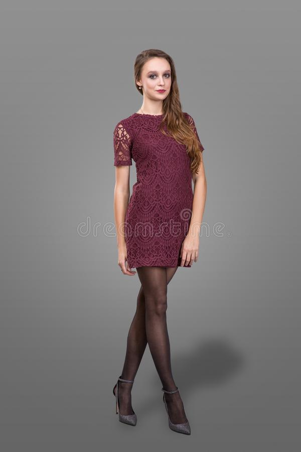 Portrait of beautiful woman on grey background. slim young woman in burgundy bodycon dress posing in studio. Portrait of beautiful woman isolated on grey stock image