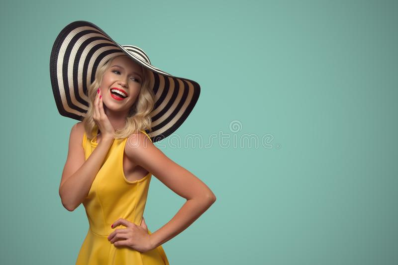 Pop art portrait of beautiful woman in hat. Blue background. royalty free stock image