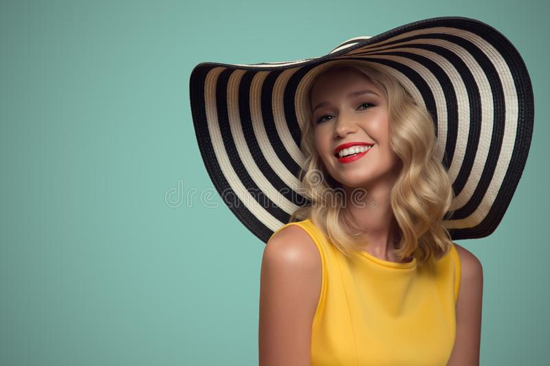 Pop art portrait of beautiful woman in hat. Blue background. stock images