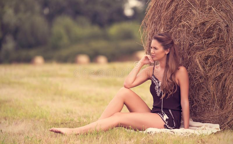 Portrait of a beautiful woman with hay bale. In summer royalty free stock images