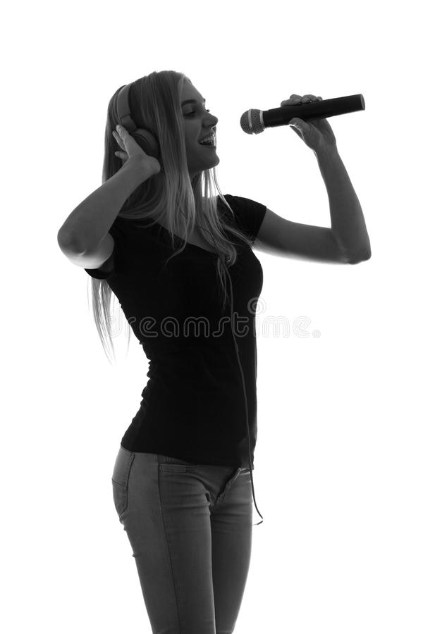 Portrait of a beautiful woman in headphones and with a microphone royalty free stock photography