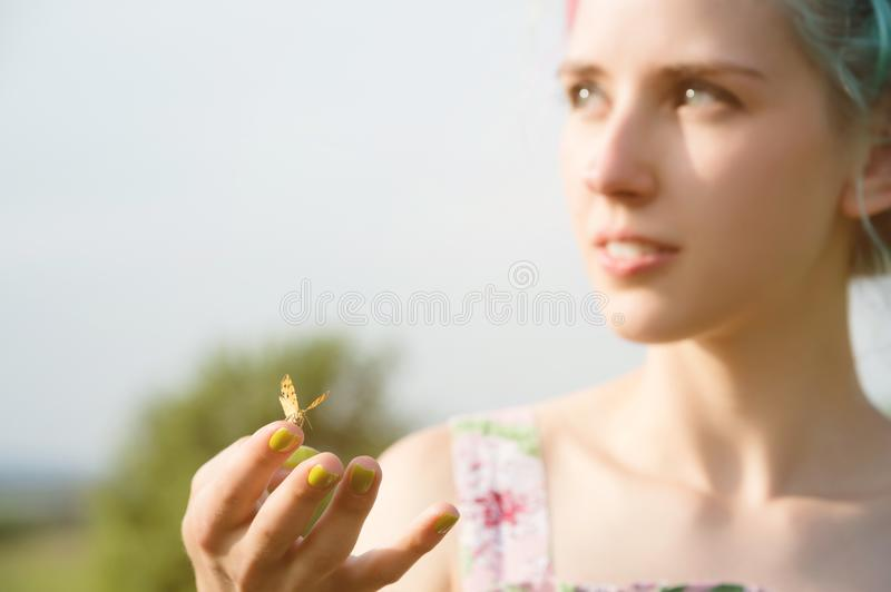 Portrait of a beautiful woman holding a butterfly on her hand in the garden. Beauty portrait. Unity with nature. Ecology. Concept royalty free stock photo