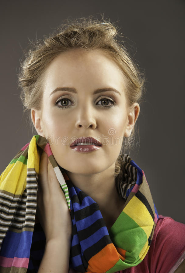 Portrait of beautiful woman holding colorful scarf to her face stock photo