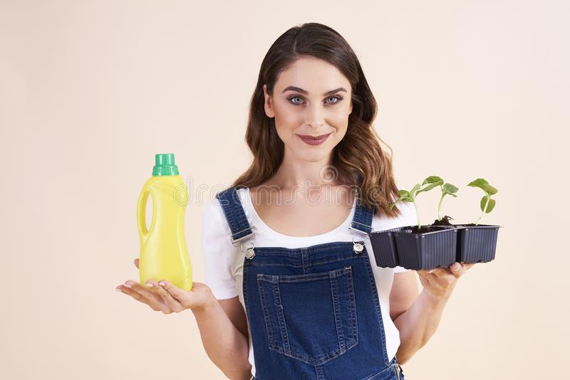 Portrait of beautiful woman holding cucumber seedling and fertilizer royalty free stock photo
