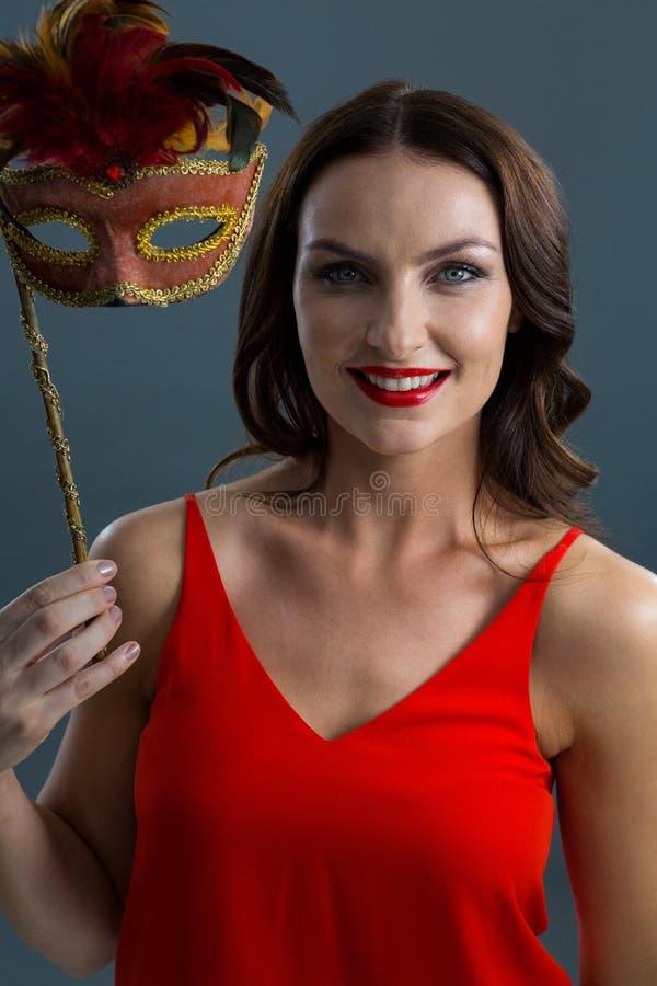 Woman holding masquerade mask against black background royalty free stock image