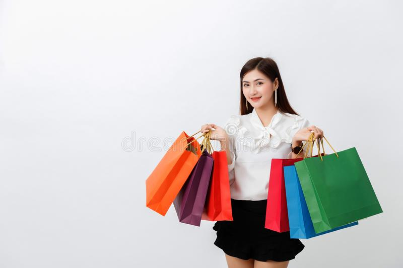 Portrait of beautiful woman holding shopping bags over white background stock photo