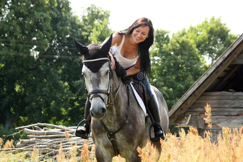 Portrait of beautiful woman on horse near the barn stock photography