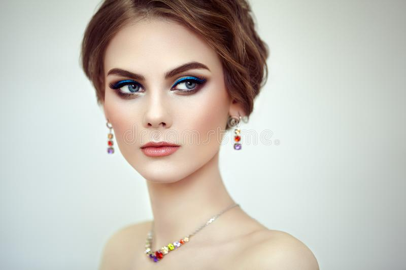 Portrait Beautiful Woman with Jewelry. Fashion Makeup and Cosmetics. Elegant Hairstyle. Blue Make-up Arrows. Beauty and Accessories stock photography