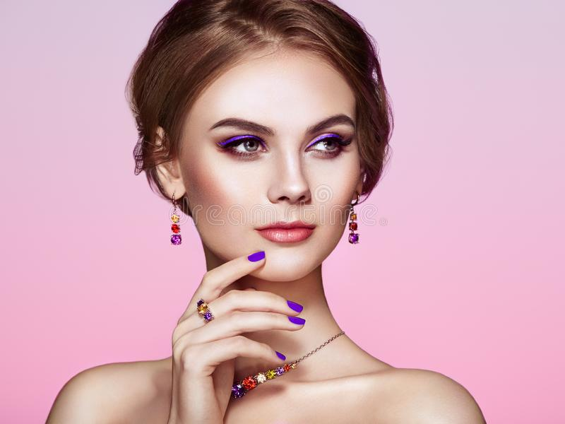 Portrait Beautiful Woman with Jewelry. Model Girl with Violet Manicure on Nails. Elegant Hairstyle. Violet Make-up Arrows. Beauty and Accessories stock images