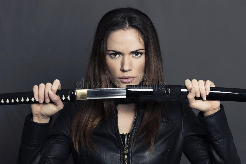 Portrait of beautiful woman with Katana. In studio stock photography