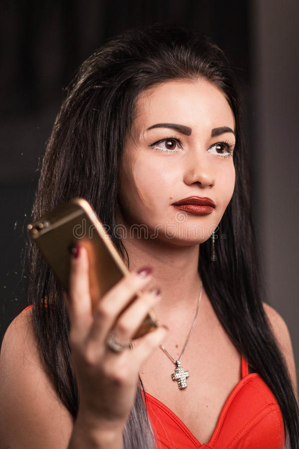 Portrait of beautiful woman with long dark hair and bright makeup holding a phone in her hand. Portrait of beautiful woman with long dark hair and bright makeup stock image