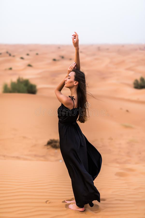Portrait of beautiful woman in long fluttering black dress posing outdoor at sandy desert royalty free stock photo