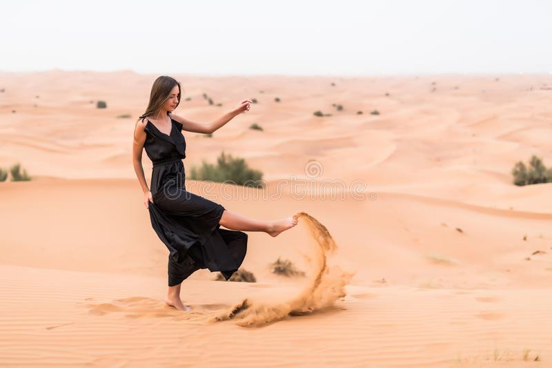 Portrait of beautiful woman in long fluttering black dress posing outdoor at sandy desert stock photos