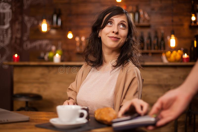 Portrait of beautiful woman looking up at barista and paying coffee using modern payment in a coffee shop royalty free stock photography