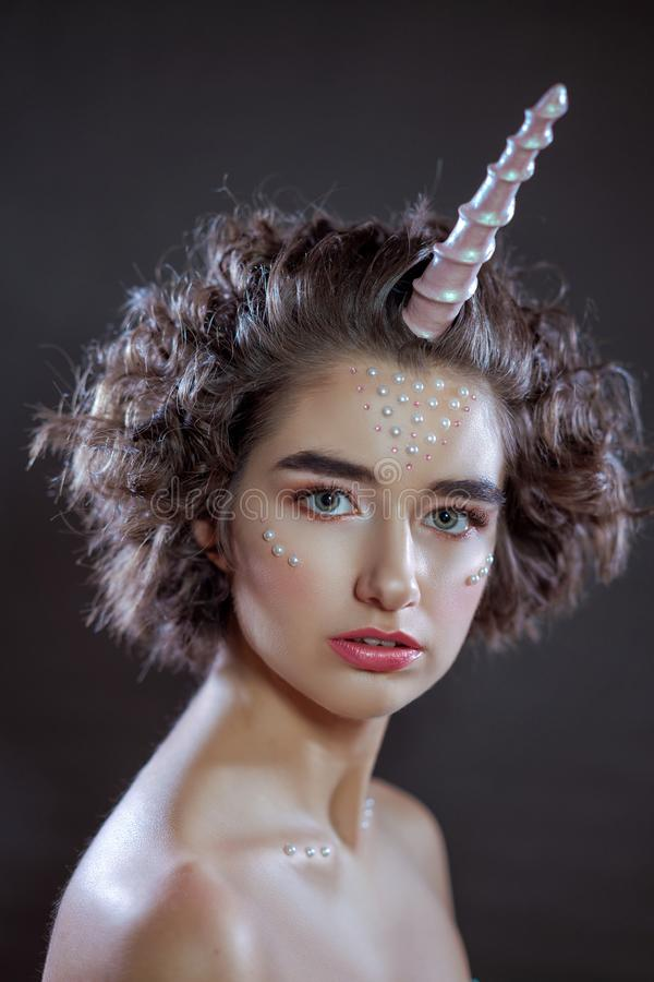 Portrait of a beautiful woman with a make-up and beads on her face , pink horn , unicorn , fashion photo shoot royalty free stock image