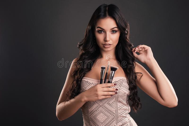 Portrait of the beautiful woman with make-up brushes near attractive face. Adult girl posing over grey background royalty free stock images
