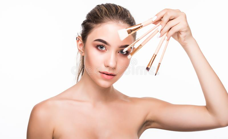 Portrait of the beautiful woman with make-up brushes near attractive face over white background stock photography