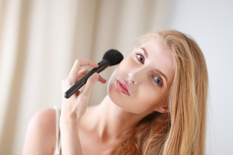 Portrait of the beautiful woman with make-up brushes near attractive face royalty free stock photography