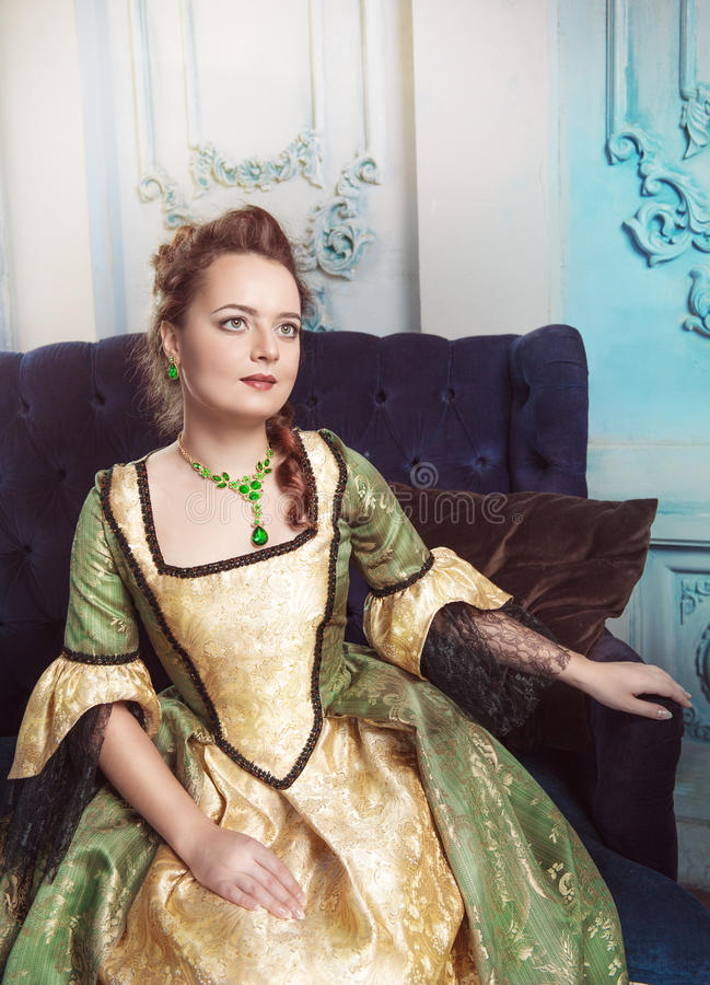 Portrait of beautiful woman in medieval dress. On the sofa stock images