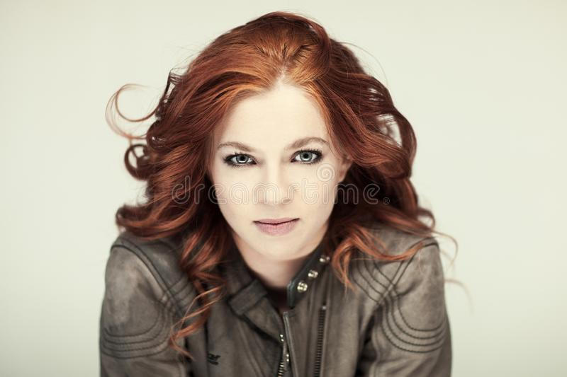 Portrait of a beautiful woman with perfect styled red curly hairand natural make up, cool, casual easy look in leather jacket, coa stock photography