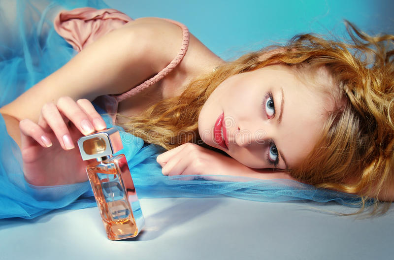 Portrait of beautiful woman with perfume bottle royalty free stock photo