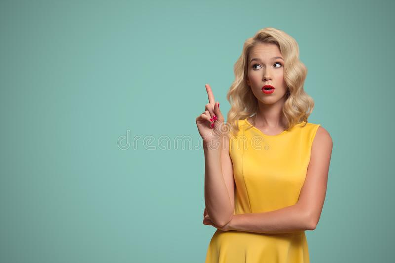Pop art portrait of beautiful woman pointing finger on copyspace. royalty free stock images