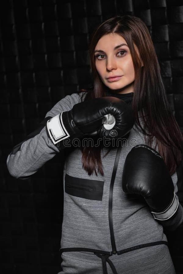 Portrait of beautiful woman. Posing in big black boxing gloves stock photography