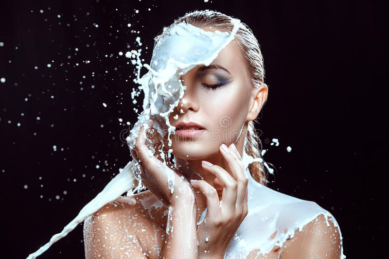 Portrait of the beautiful woman poured by milk stock image