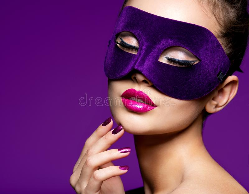Portrait of a beautiful woman with purple nails and violet theatre mask on face. Portrait of a beautiful  woman with purple nails and violet theatre mask on face royalty free stock image
