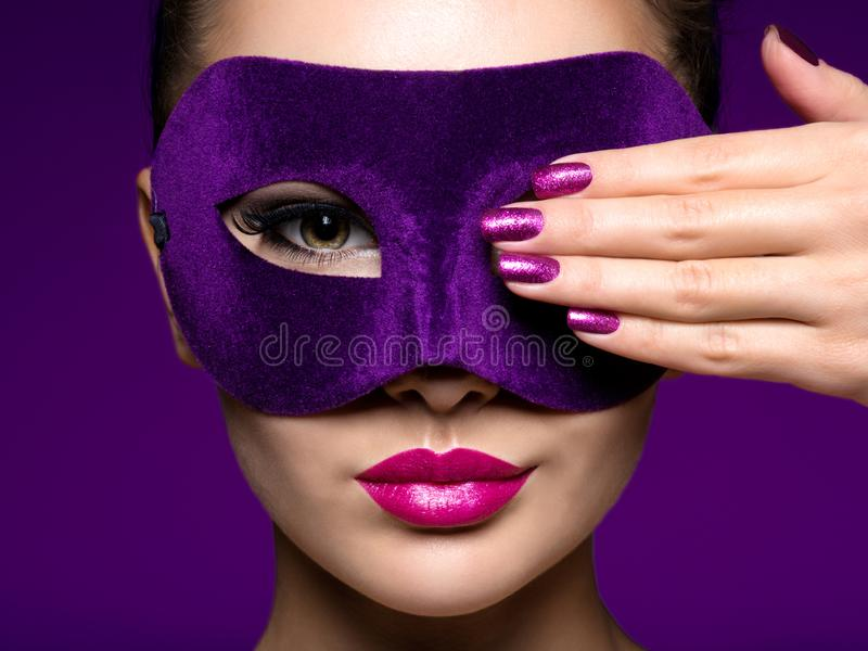 Portrait of a beautiful woman with purple nails and violet theatre mask on face. Portrait of a beautiful  woman with purple nails and violet theatre mask on face stock images