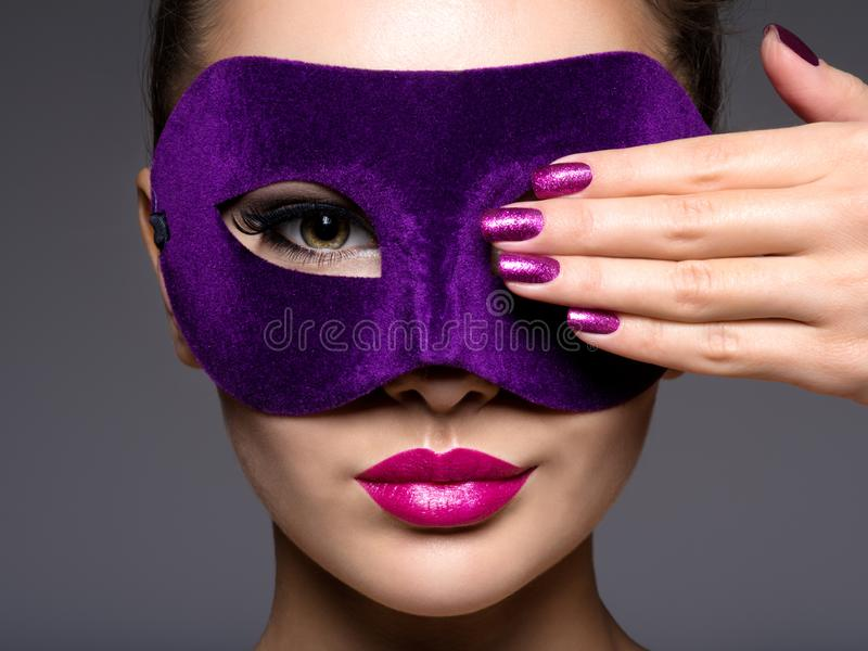 Portrait of a beautiful woman with purple nails and a violet theatre mask on face. Portrait of a beautiful  woman with purple nails and violet theatre mask on stock image