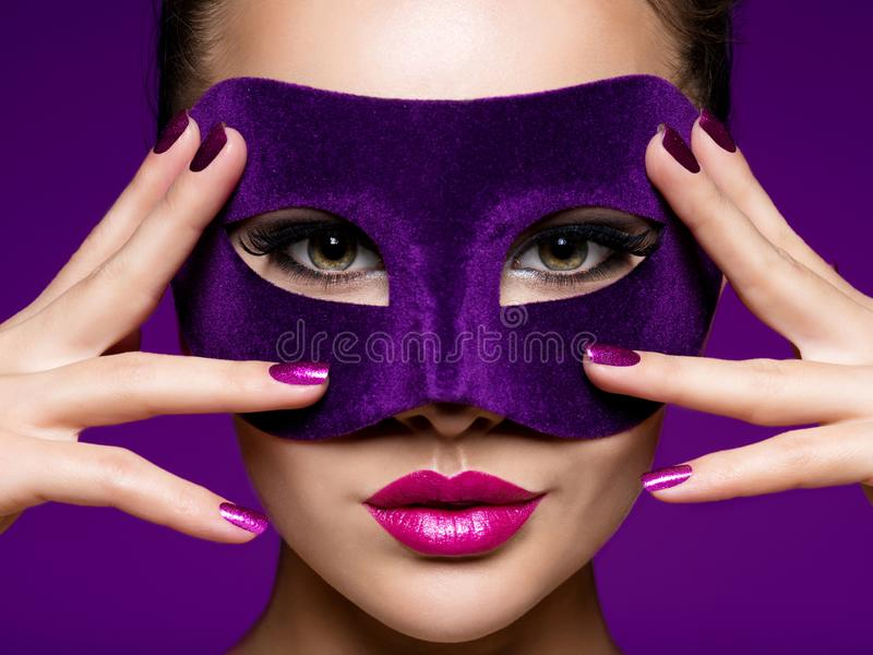 Portrait of a beautiful  woman with purple nails and violet theatre mask on face. Portrait of a beautiful woman with purple nails and violet theatre mask on face royalty free stock photography