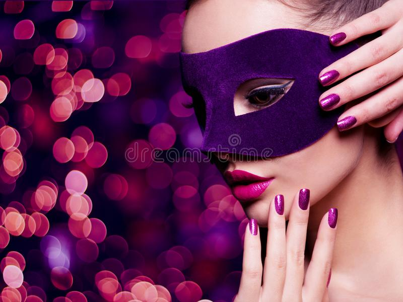 Portrait of a beautiful woman with purple nails and violet theatre mask on face. Portrait of a beautiful  woman with purple nails and violet theatre mask on face stock photo