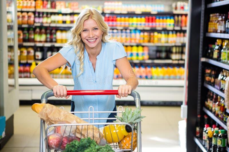 Portrait of beautiful woman pushing cart royalty free stock photo