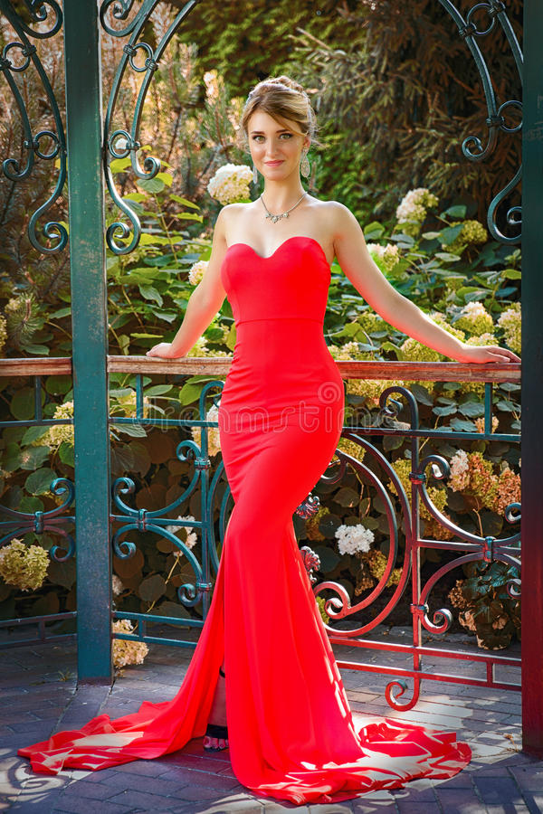 Portrait of beautiful woman in red dress outdoor. In alcove royalty free stock photo