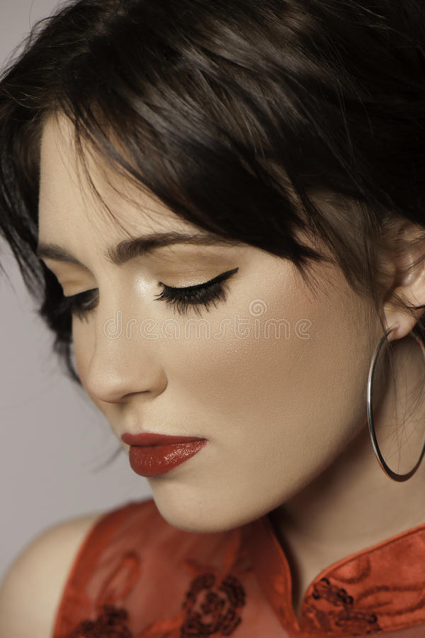 Portrait of beautiful woman in red looking down. Portrait of a beautiful woman with dark hair wearing red lipstick, black eyeliner, silver hoop earrings, and a royalty free stock photos